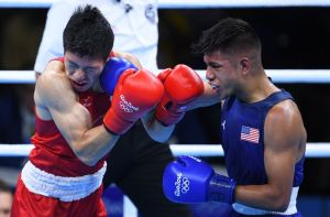 Aug 9, 2016; Rio de Janeiro, Brazil; Daisuke Narimatsu (JPN, red gloves) competes with  JR. Carlos Zenon Balderas (USA, blue gloves) during the men's light preliminaries in the Rio 2016 Summer Olympic Games at Riocentro - Pavilion 6. Mandatory Credit: Jack Gruber-USA TODAY Sports