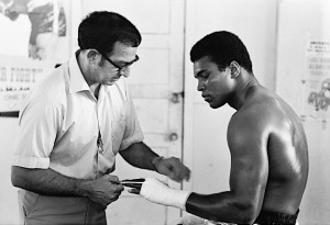 Muhammad Ali getting his hands wrapped by trainer Angelo Dundee before training session at the 5th Street Gym. Miami Beach, Florida 10/9/1970 (Image # 2045 )