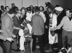 Sonny Liston (3R), at weighting-in ceremonies before world championship fight with Cassius Clay (L, sitting).